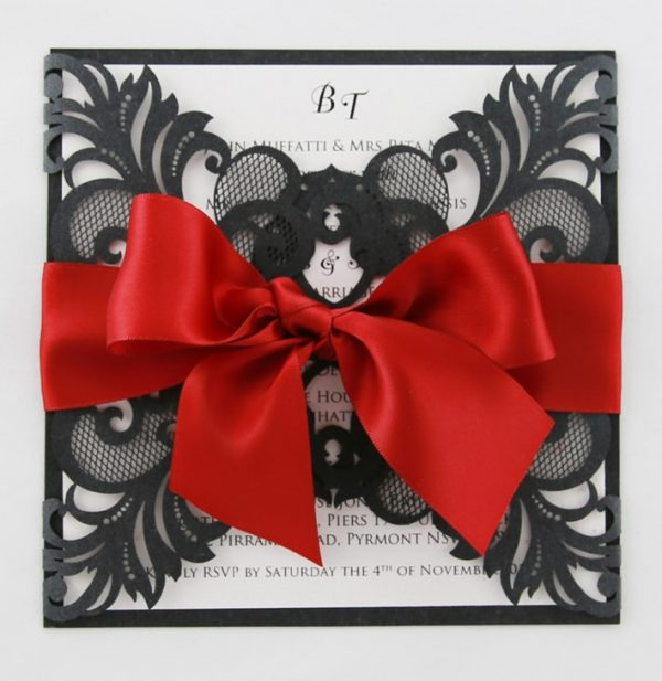WEDINV130 frontof black lasercut invitation with red ribbon and white insert