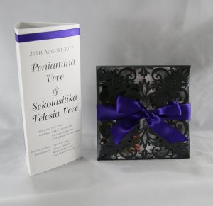 Black laser cut invitation with purple ribbon and white insert white and purple tri fold table menus